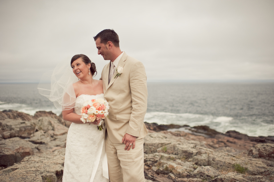 Bride and groom on ocean rocks