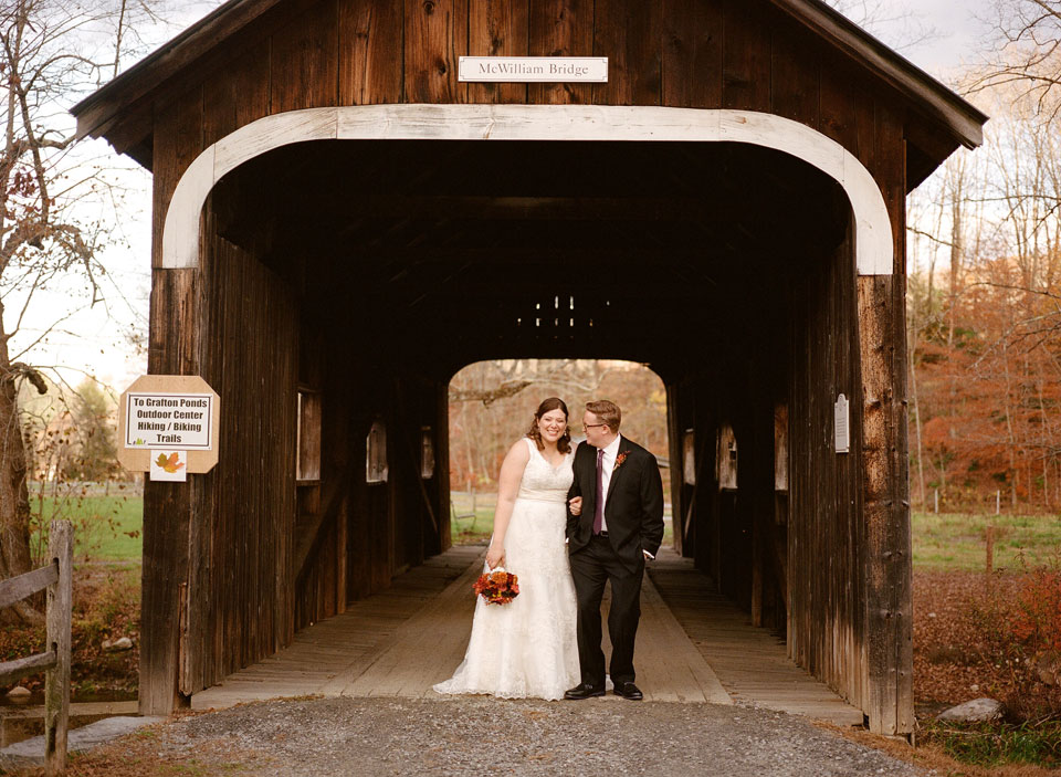 bride and groom in covered bridge vermont fall wedding
